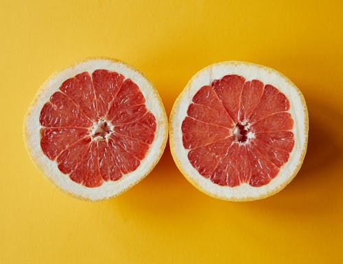 在黃色表面上切成薄片的橙色水果