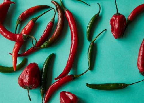 Top view of various types of fresh ripe colorful chili peppers scattered on light blue background
