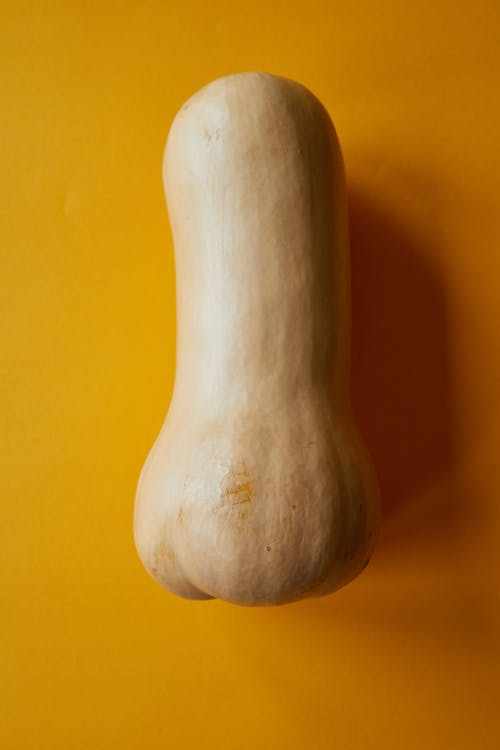 From above of ripe fresh butternut squash placed on orange background in daylight