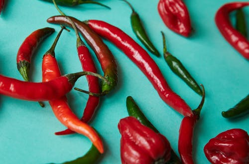 High angle assortment of fresh ripe sweet and chili colorful peppers placed on light blue surface