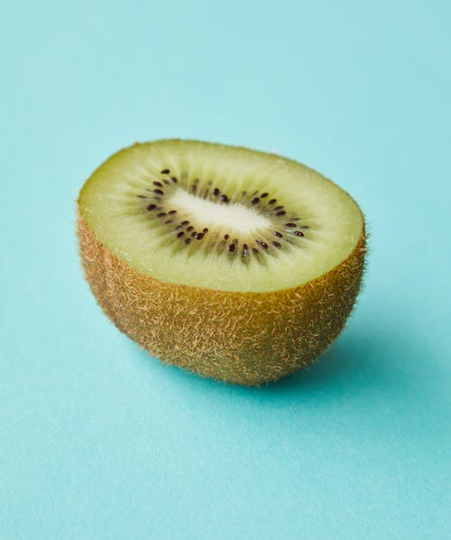 Cut juicy kiwi on blue surface
