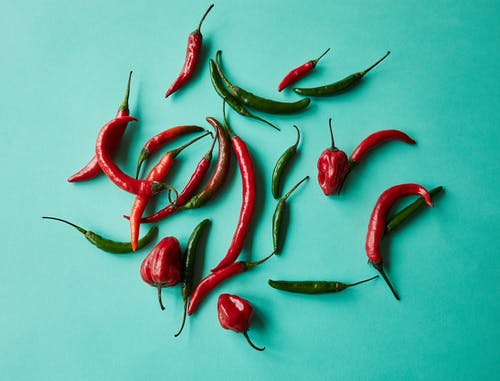From above of red and green various chili peppers scattered on blue background