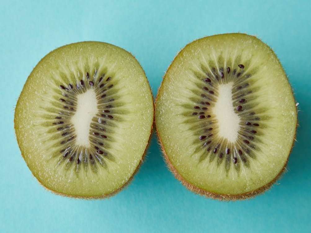 From above of green halves of kiwi with black seeds placed on blue background