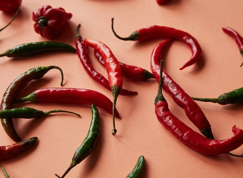 Different ripe red and green spicy chili peppers lying on coral background in bright studio