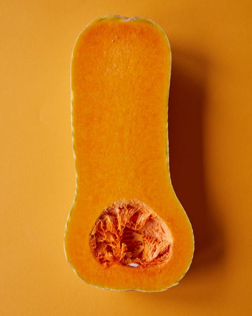 Top view composition of bright fresh ripe half of butternut squash placed on orange surface