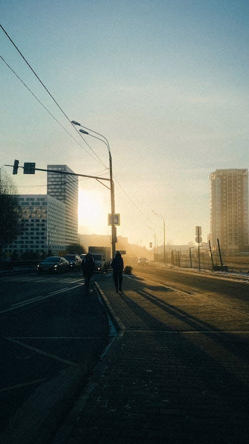 Silhouettes of people walking along asphalt road in morning