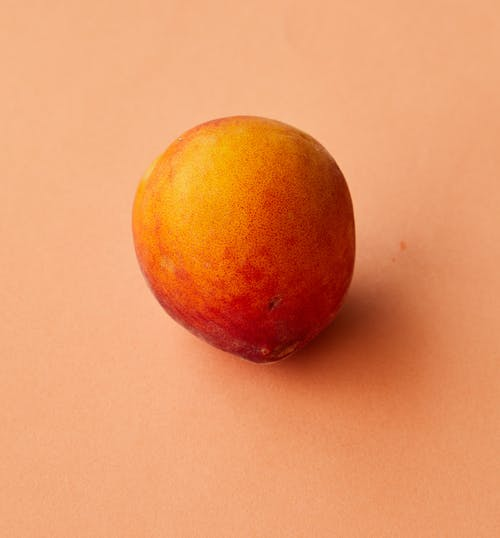 High angle of whole healthy ripe peach placed on beige background in studio