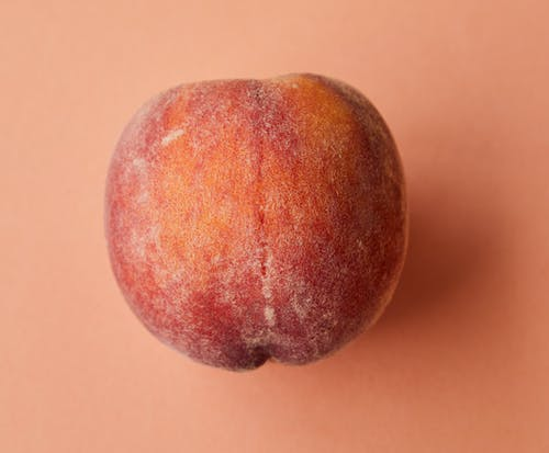 Красный круглый фрукт на белой поверхности