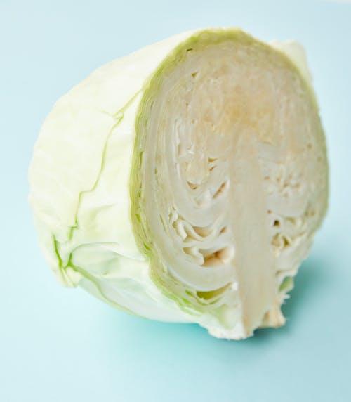 Cut fresh white cabbage on blue background