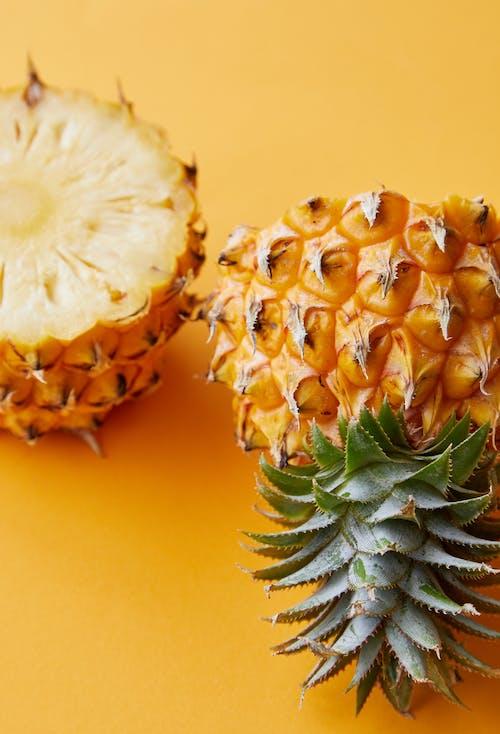 Плоды ананаса на желтой поверхности