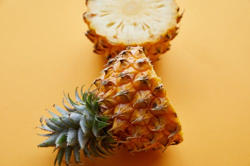 From above of fresh textured half cut pineapple on bright yellow background of studio