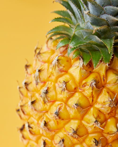 Tasty ripe pineapple with rough verdant leaves on bright yellow background of studio