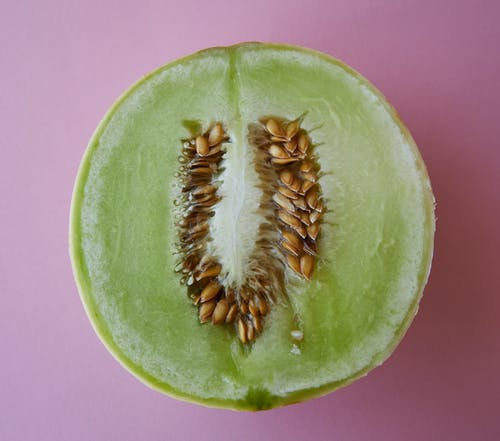 Top view of fresh half cut melon with seeds placed on pink background