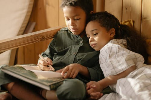A Girl Watching Her Brother Write on a Paper