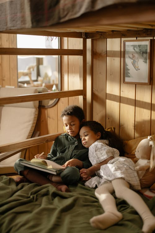 A Girl Watching Her Brother Write on a Book
