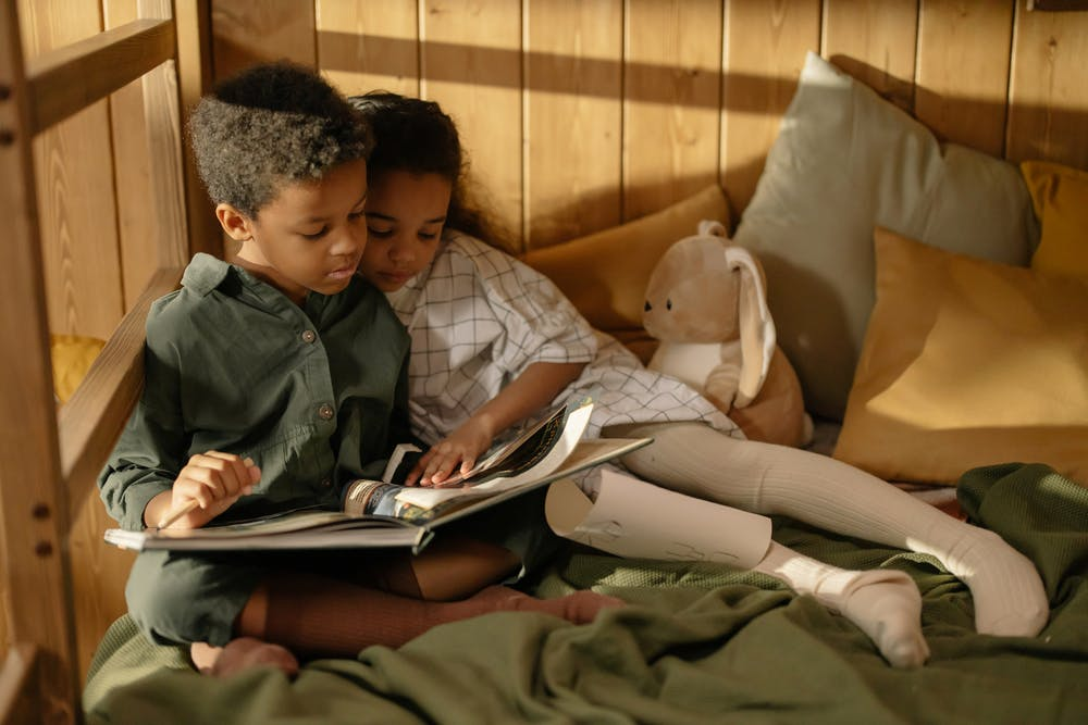 Two children reading a fairy tale book. | Photo: Pexels