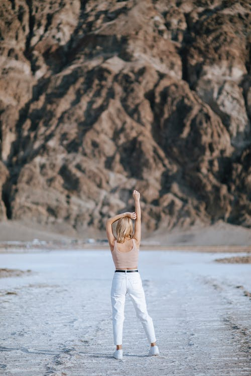 Woman in Brown Long Sleeve Shirt and White Pants Standing on White Sand