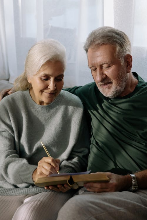 Man in Gray Sweater Sitting Beside Woman in Green Sweater