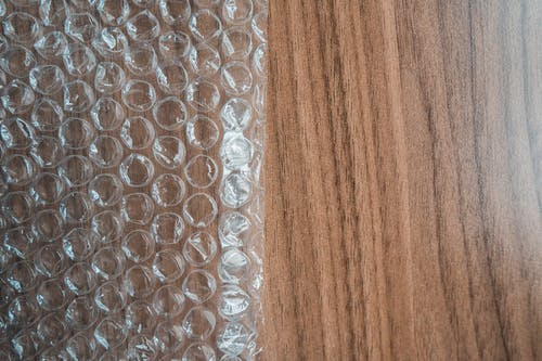 Top view of bubble wrap sheet with uneven surface on smooth wooden desk in shiny light