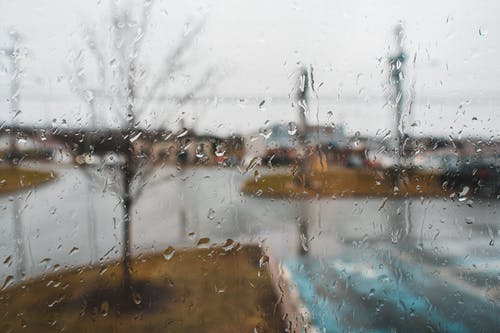 Glass wall with transparent aqua drips and fluids against urban street on rainy day in autumn