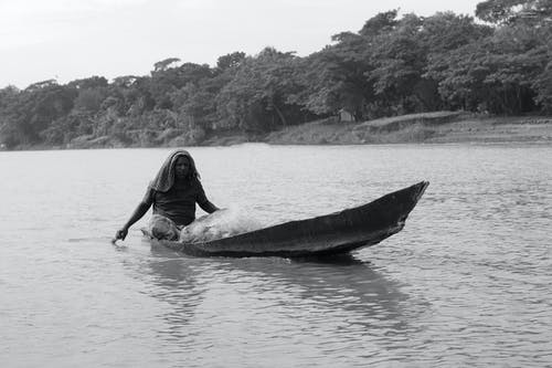 Woman in Black Dress Lying on Black and White Surfboard on Body of Water