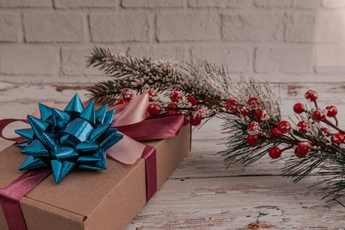 High angle of carton gift box tied with ribbon bow placed on wooden table near Christmas tree branch with snowflakes and red berries