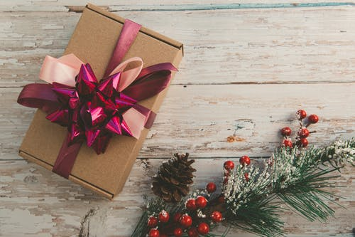 From above elegant gift box with ribbon bows placed on rough wooden table near branch of green Christmas tree with red berries and cone