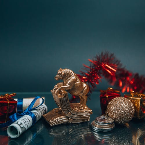 Shiny golden bull figurine and bauble arranged with money during New Year holiday