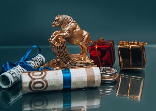 Golden ox figurine with small wrapped New Year presents composed with coins stack and rolled various banknotes