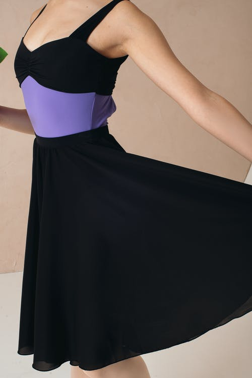 Crop anonymous slim female in black and violet wear touching bottom of dress while dancing in studio