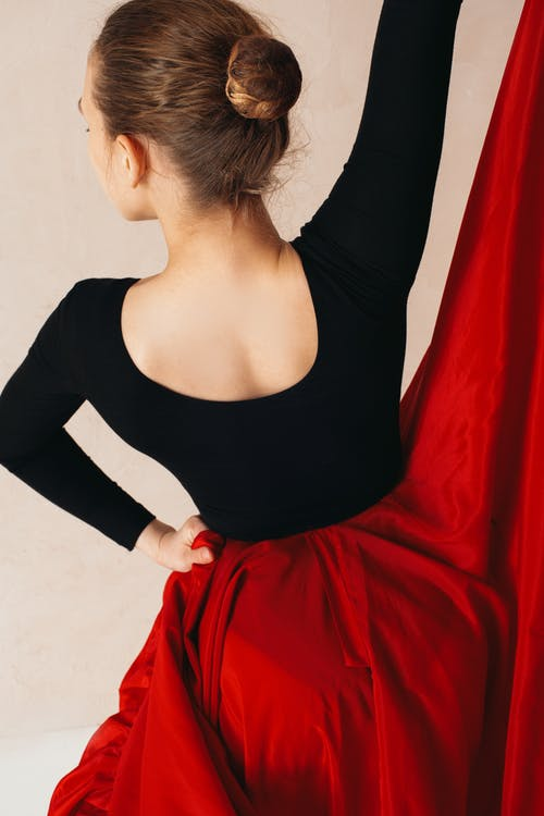 Back view of anonymous young female flamenco dancer in big red skirt with raised hand on cream background
