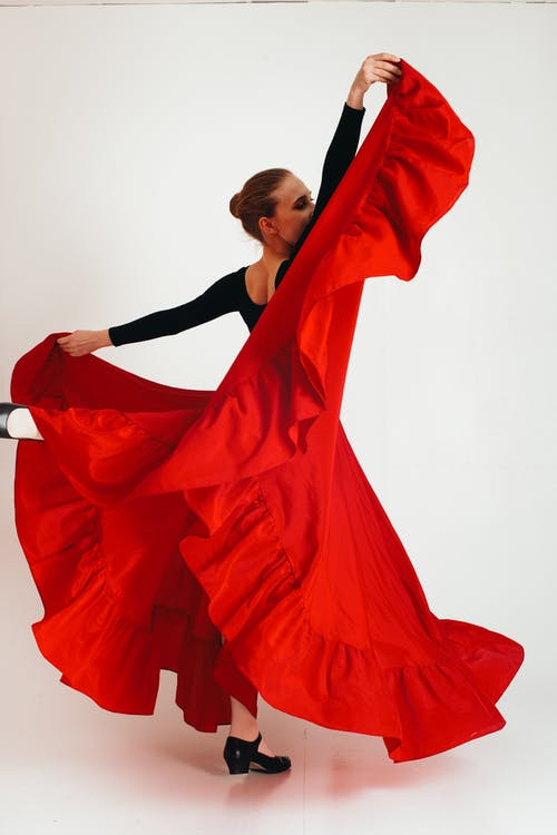Full body young female flamenco dancer standing with raised leg and hands against white background
