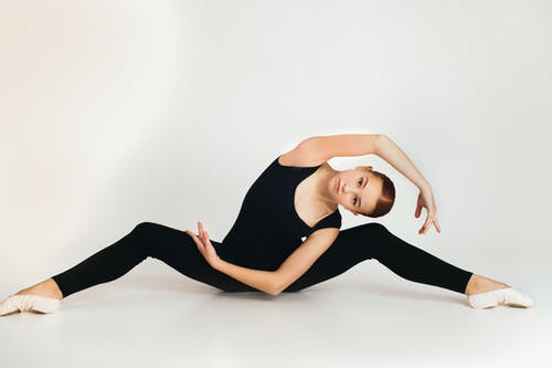 Young flexible female in black outfit and pointes stretching while practicing yoga and looking at camera in studio on white background