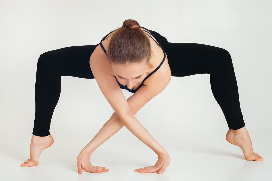 Full length young female in black wear practicing yoga in studio on white background