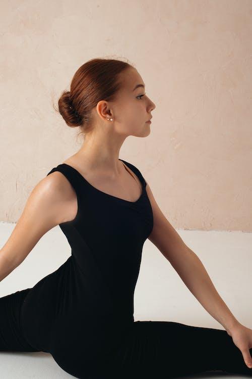 Slim woman stretching in studio