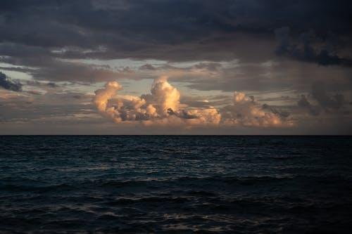 Sea Waves Under Dark and White Clouds