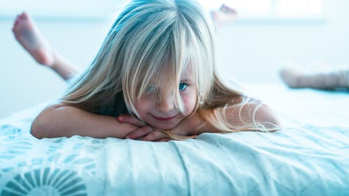 Girl With Blue Hair Lying on Bed