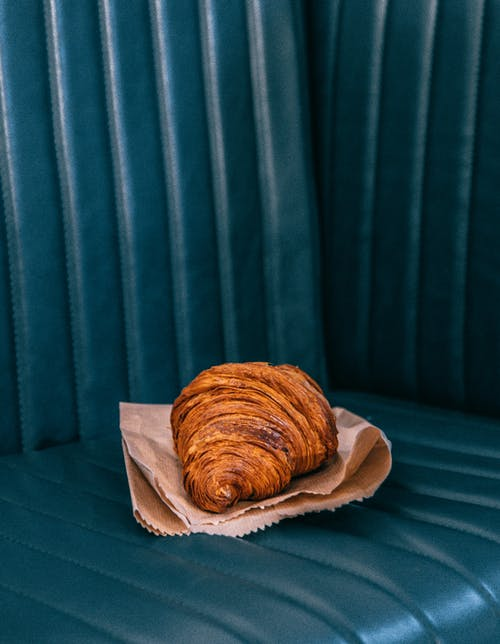 Tasty freshly baked croissant on parchment paper placed on dark leather sofa in daylight