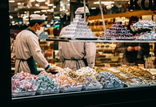 白色長袖襯衫和黑色的褲子,站在食物展示前的人