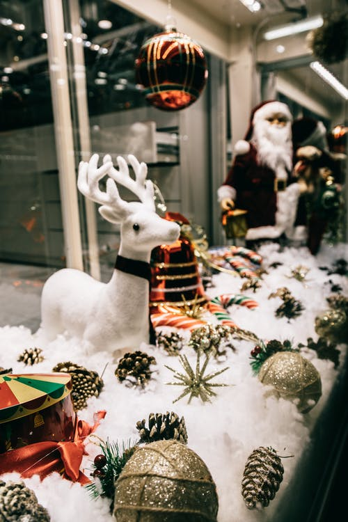 Store window with festive decorations including sparkling baubles deer and Santa figurines placed on fluffy artificial snow