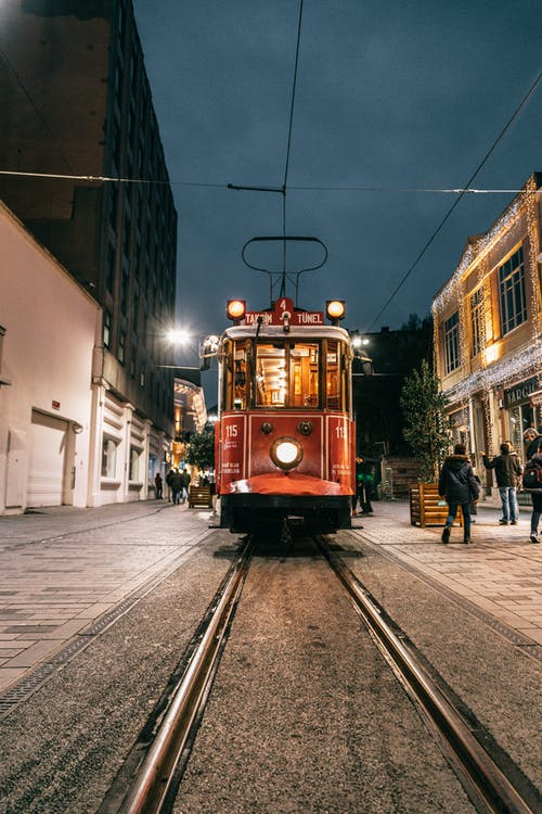 Vintage tramway riding on rails along people walking on paved sidewalk at night