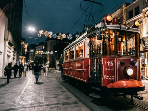 Old tram riding on railway of city decorated with garlands