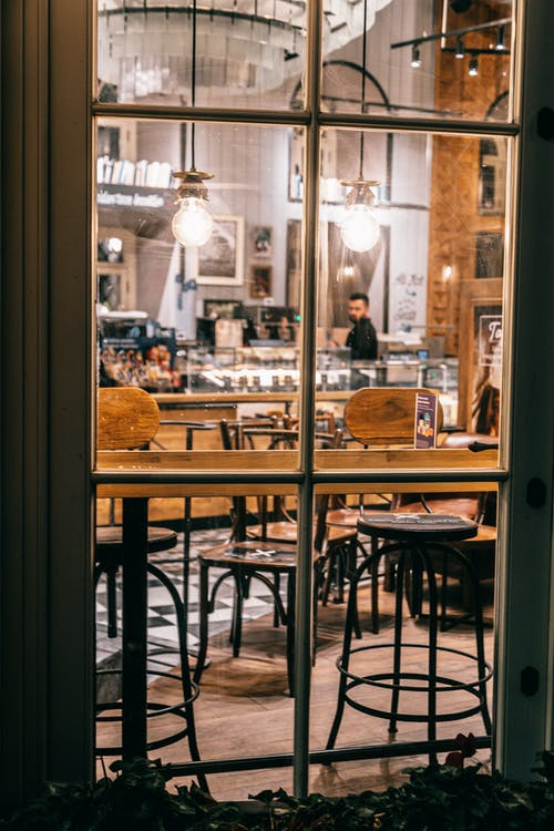 Through glass interior of cafe with wooden furniture and barista working at counter