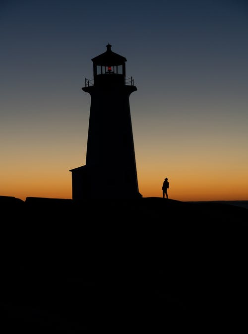 Unrecognizable tourist silhouette against lighthouse at sunset