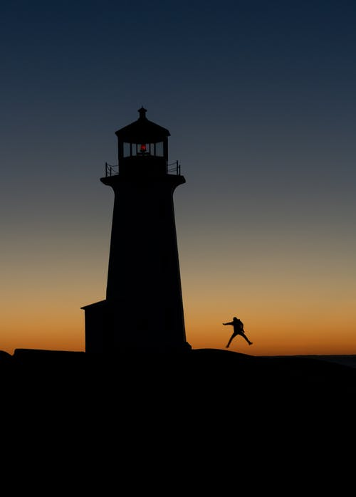 Anonymous traveler jumping with legs apart against lighthouse silhouette and bright sky at night