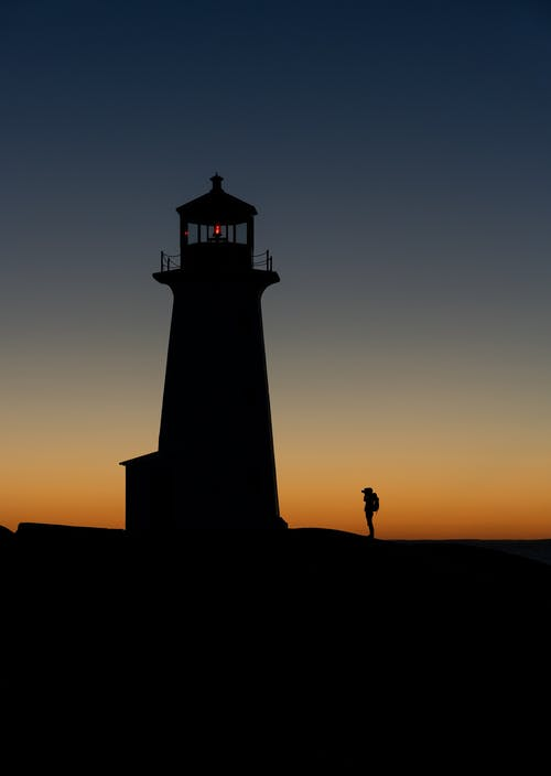 Unrecognizable backpacker silhouette against lighthouse at dusk