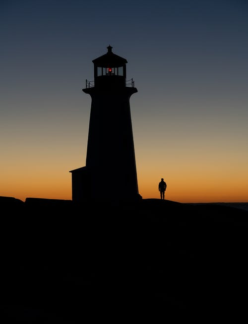 Scenic view of anonymous lonely tourist silhouette against beacon admiring bright sky during trip in twilight