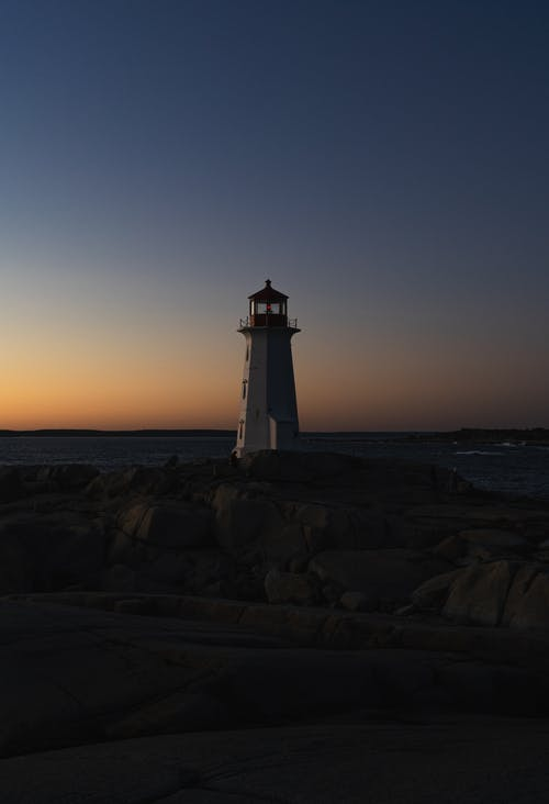 White and Black Lighthouse on Brown Rocky Shore during Sunset