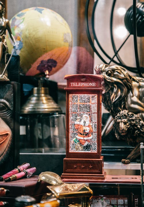 Through glass of souvenir in form of telephone booth with snow falling on Santa Claus