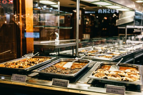 Different hot dishes in big bowls selling in self service restaurant at night